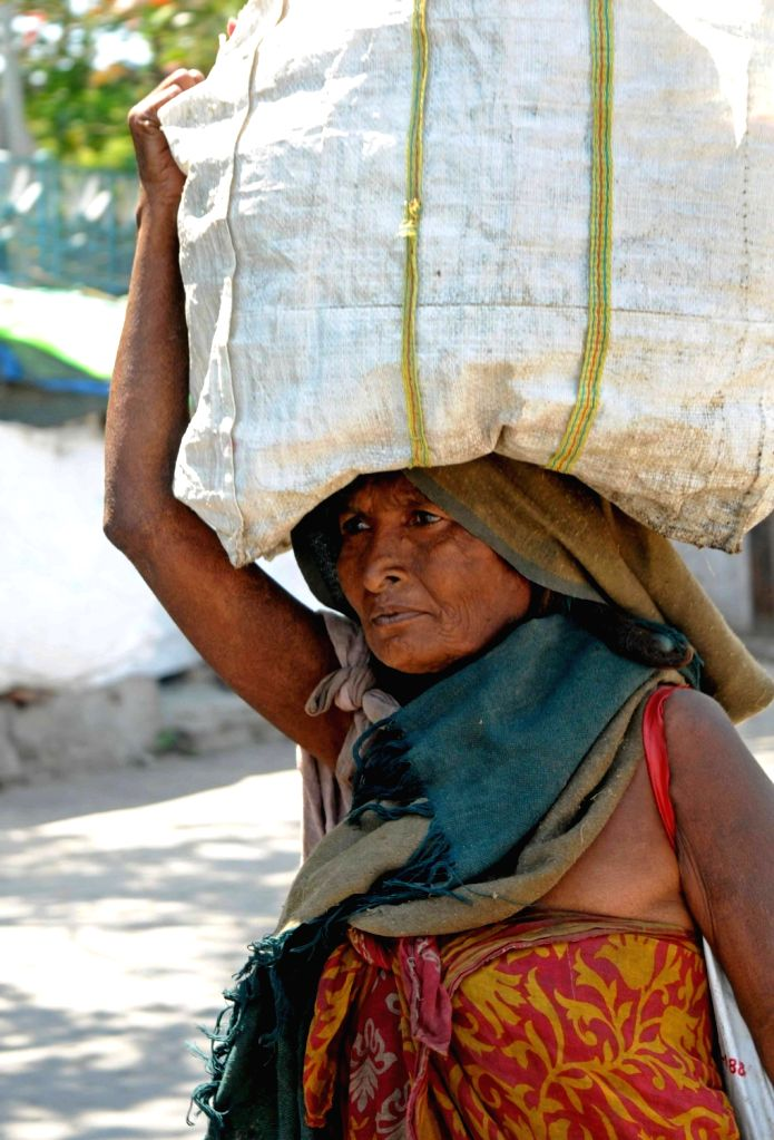 A woman carries a bag on her head as she heads back to her shelter after purchasing essential commodities on Day 5 of the 21-day countrywide lockdown imposed to contain the spread of novel ...