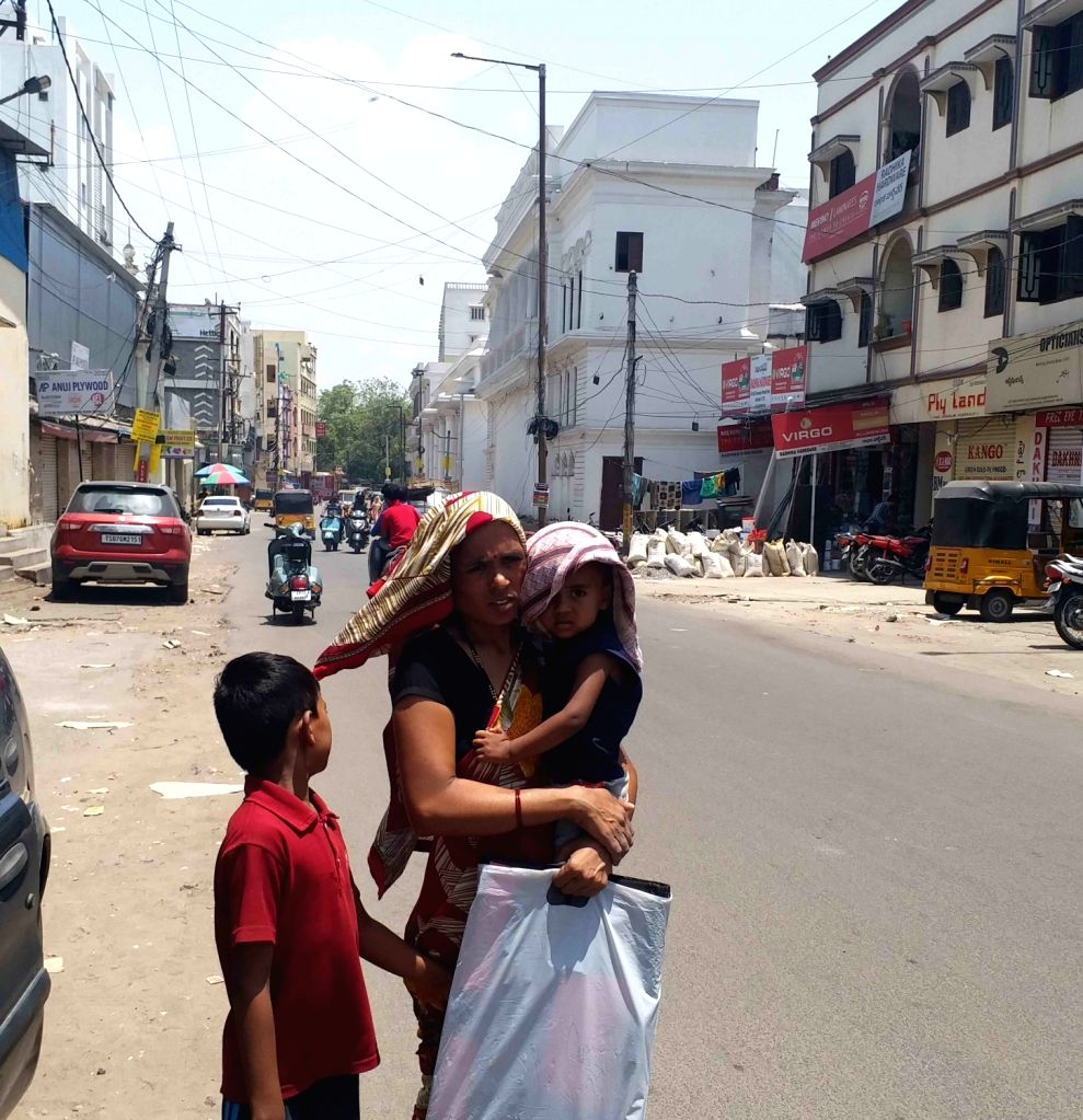 A woman carrying her child, use scarfs to shield themselves from scorching sun on a hot day, in Hyderabad, on May 26, 2019.