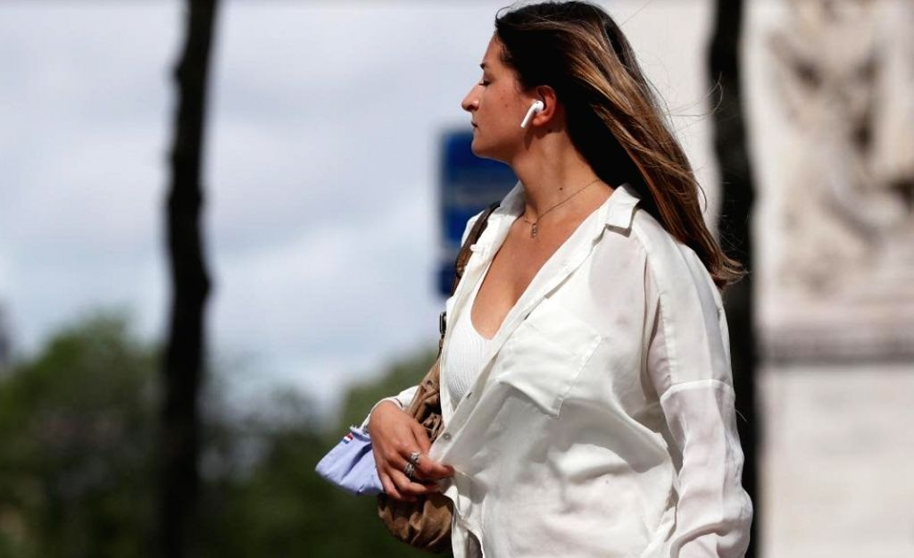 A woman carrying her mask on wrist walks on the Champs Elysees Avenue in Paris, France, June 17, 2021. French Prime Minister Jean Castex on Wednesday announced that people could stop wearing face ... - Jean Castex