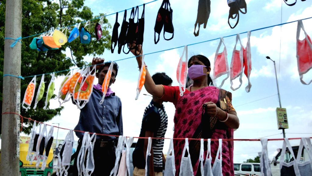 A woman checks out colorful masks being sold at a streetside stall in Agartala during the extended nationwide lockdown imposed to mitigate the spread of coronavirus; on Apr 26, 2020.