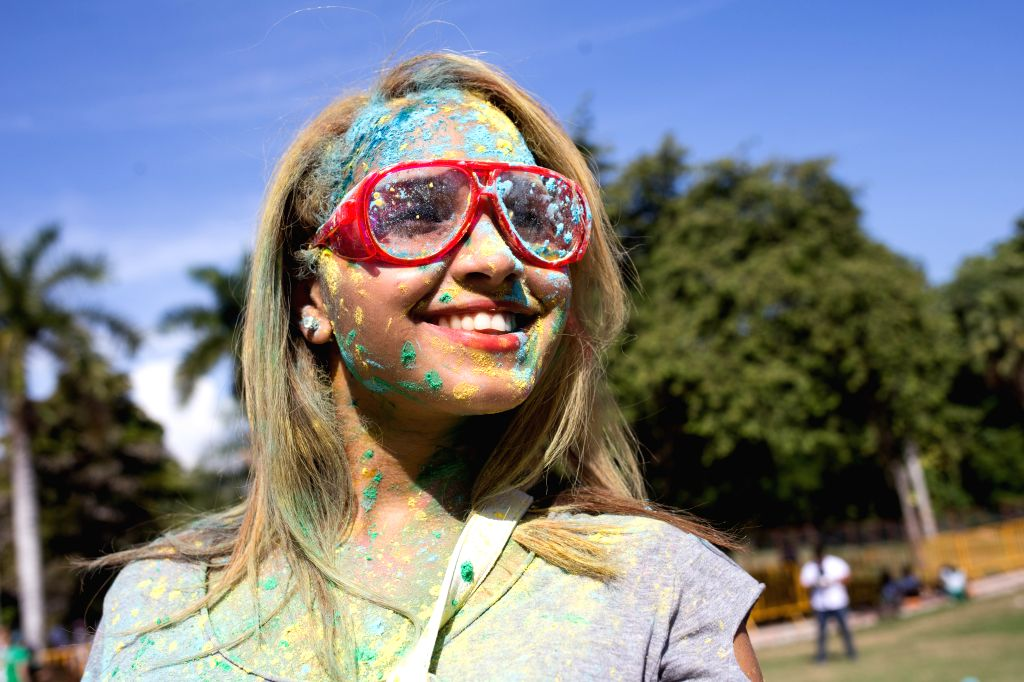 A woman covered with colored powder takes part in the Holi Sun Festival of Colors in Santo Domingo, Dominican Republic, on Aug. 15, 2015.(Xinhua/Fran Afonso) ...