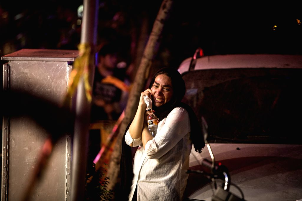 A woman cries at the explosion site in Tehran, Iran, June 30, 2020. At least 19 people were killed in an explosion at a clinic in the northern district of Iran's ...