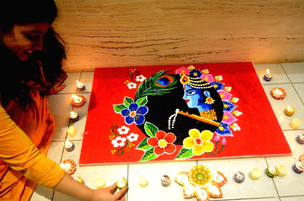 A woman decorates her rangoli with earthen lamps on the eve of Diwali, at her residence in Kolkata on Nov 13, 2020.