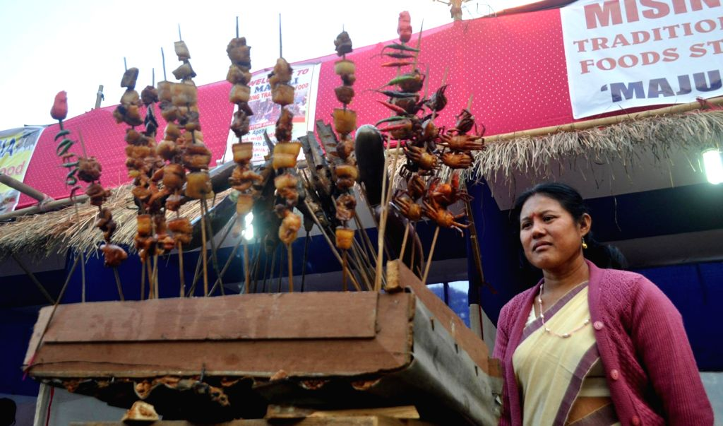 A woman displays ethnic food of Assam on the first day of the North East Ethnic Food Festival in Guwahati on Dec.15, 2013.