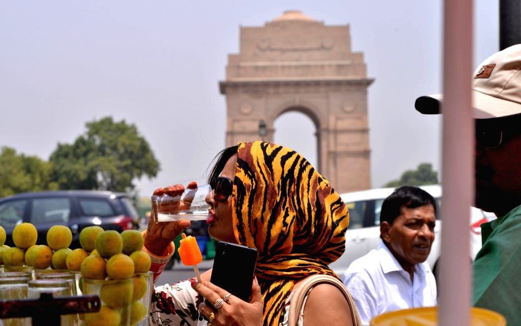 A woman drinks lemonade to beat the heat on a hot day in New Delhi on May 23, 2018.