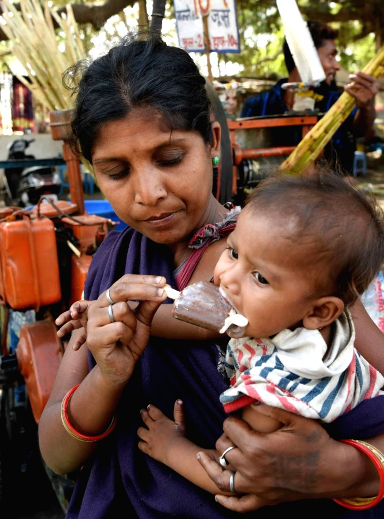 A woman feeds an ice-cream to her child on a hot sunny day in Patna, on April 15, 2019.