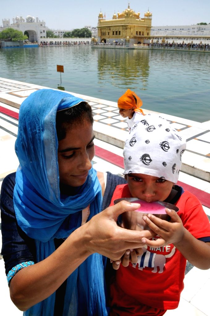 A woman feeds her child with sweetened water distributed on the martyrdom day of Guru Arjan Dev at the Golden Temple in Amritsar, on June 7, 2019. - Arjan Dev
