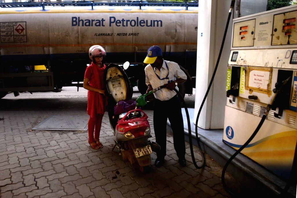 A woman gets the petrol tank of her two-wheeler filled at a petrol pump, in Kolkata on Sept 3, 2018. Prices of petrol and diesel, already at unprecedented levels in the country, rose for the ...