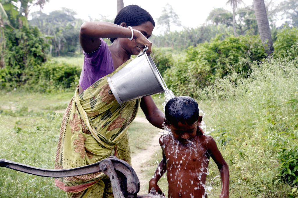 A woman gives her child a bath at a hand pump on the occasion of Mother's Day during the extended nationwide lockdown imposed to mitigate the spread of coronavirus, in Noida on May 10, 2020.