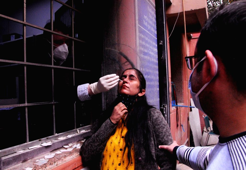 A woman gives swab samples for COVID-19 testing at the District magistrate office (SDM) Lajpat Nagar, in New Delhi on Nov 24, 2020.