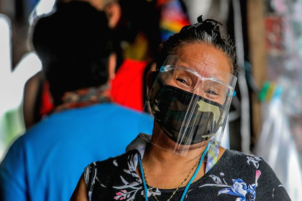 A woman has her face protected at a market in Manila, the Philippines on Aug. 14, 2020.   The number of confirmed COVID-19 cases in the Philippines surged to 153,660 ...