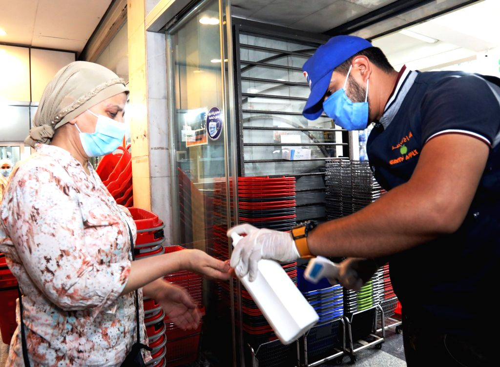 A woman has her hands disinfected at the entrance to a shopping center in Baghdad, Iraq, Aug. 13, 2020. The Iraqi Health Ministry on Thursday recorded 3,841 new ...