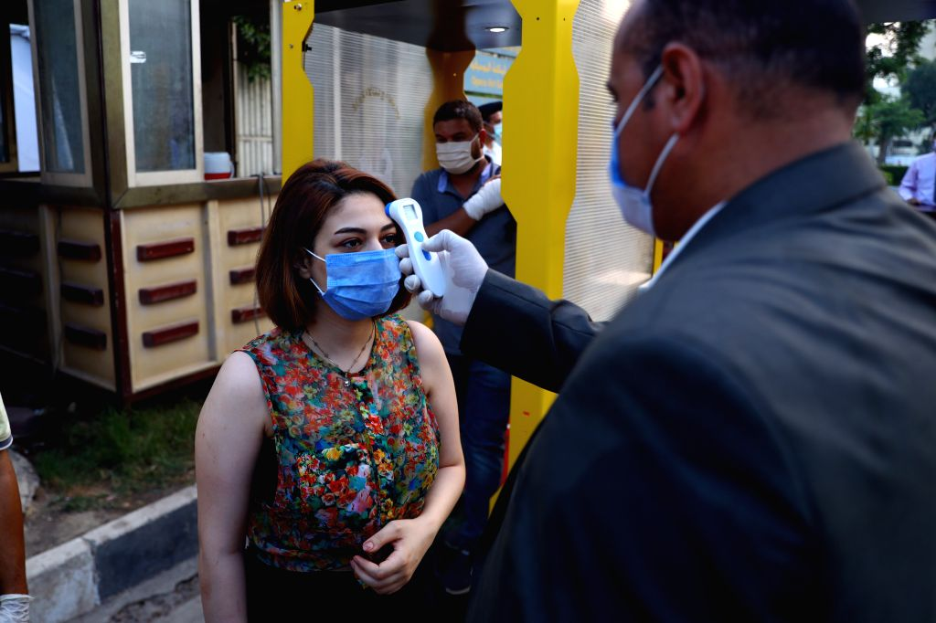 A woman has her temperature checked before entering Cairo Opera House in Cairo, Egypt, on July 9, 2020. The Cairo Opera House reopened on Thursday for about 400 ...