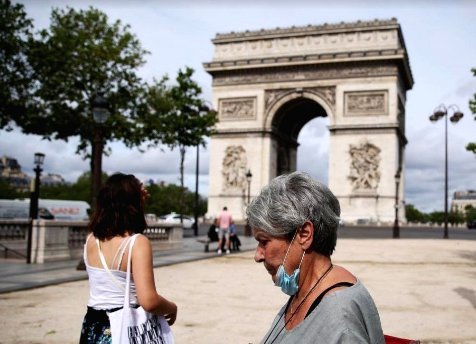 A woman holding her mask in hand walks near the Arc de Triomphe in Paris, France, June 17, 2021. French Prime Minister Jean Castex on Wednesday announced that people could stop wearing face masks ... - Jean Castex