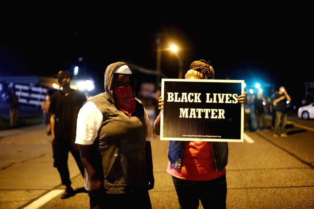 "A woman holds up a sign which reads ""Black Lives Matter"" in the street in Ferguson, Missouri, the United States, on August 10, 2015. A state of emergency ..."