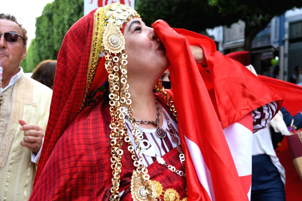 A woman in Tunisian folk costumes kisses a Tunisian national flag during celebrations of the annual National Women's Day in downtown Tunis, Tunisia, Aug. 13, 2020.