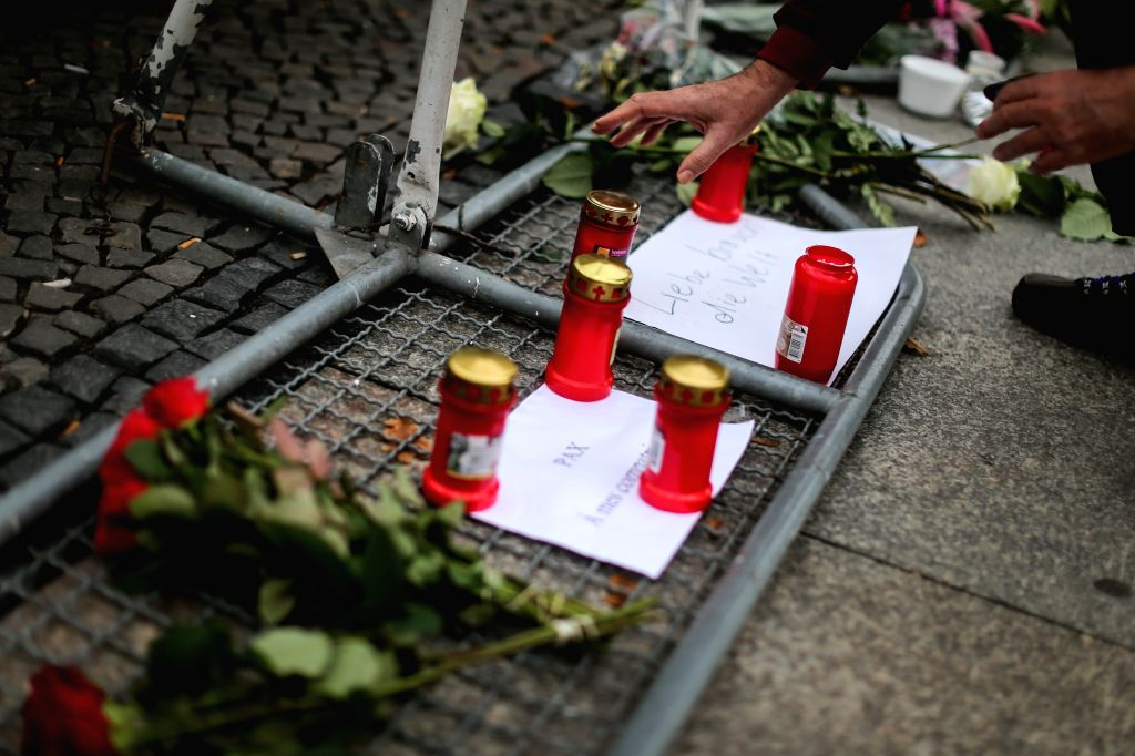 A woman lays candles outside the French Embassy in Berlin, Germany, on Nov. 14, 2015. Over 100 people were killed in a mass hostage-taking at a Paris concert hall ...