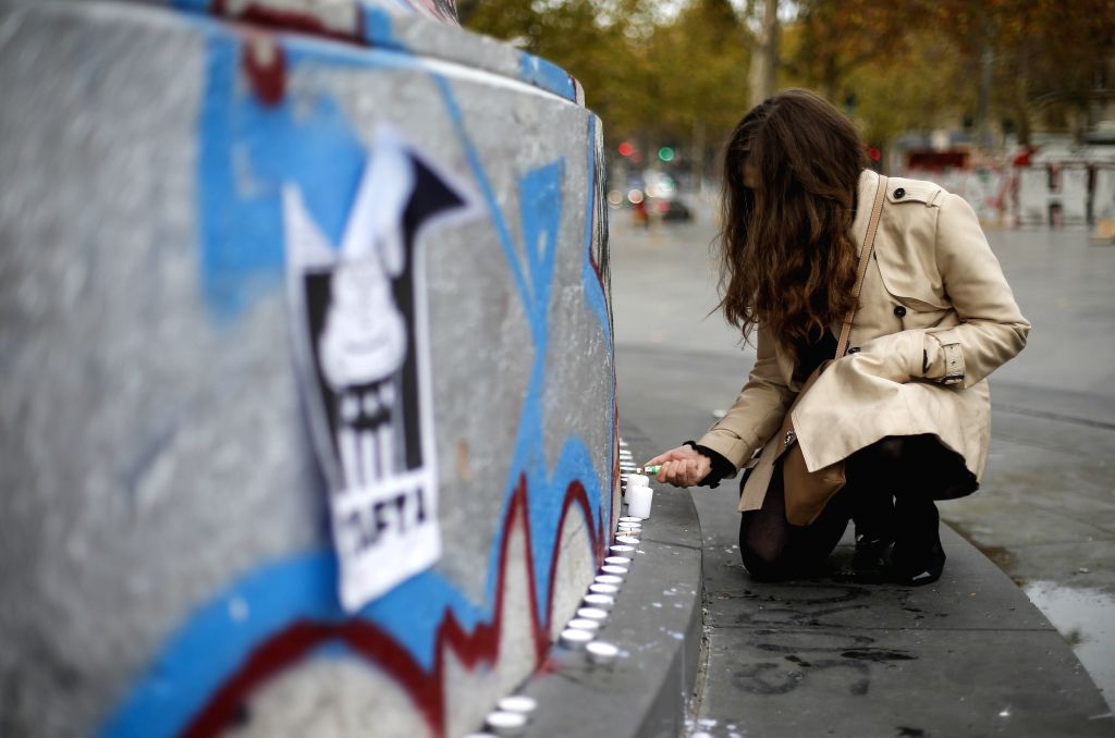 :A woman lights candles in Paris, France, on Nov. 14, 2015. Over 100 people were killed in a mass hostage-taking at a Paris concert hall Friday and many more were ...