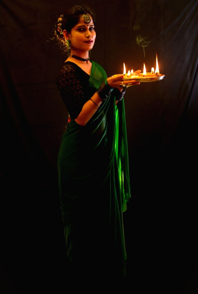 A woman lights up earthen lamps at her residence on the occasion of Diwali in Patna on Nov 14, 2020.
