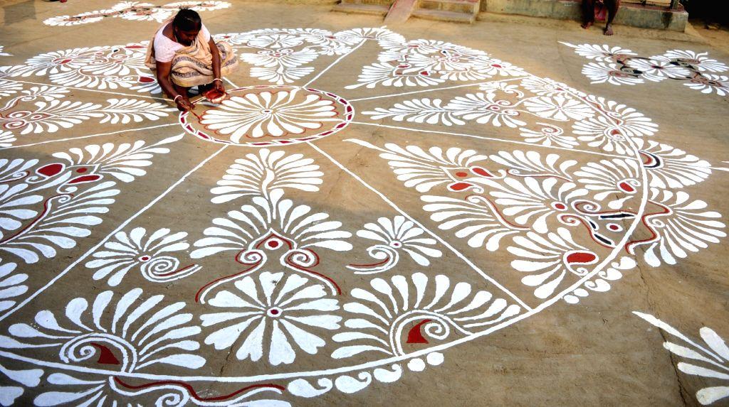 A woman makes alpana - colourful motifs - in her courtyard ahead of Makar Sankranti in Agartala, on Jan 14, 2016.