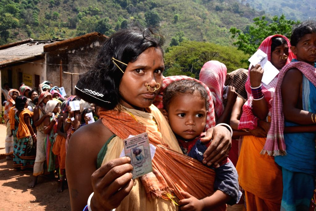 A woman of Dongaria Kondh tribe with her child at a polling station to cast her vote during the first phase of 2019 Lok Sabha polls, at Bissam Cuttack, in Odisha's Rayagada district, on ...
