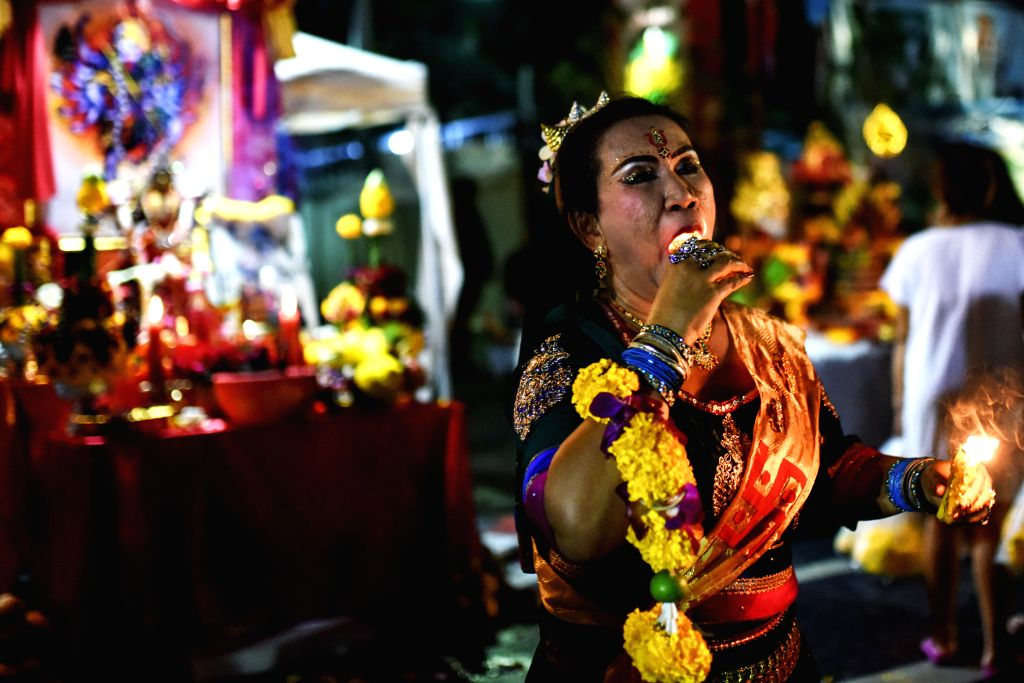 A woman performs a fire show during a Dussehra celebration in downtown Bangkok, Thailand, Oct. 22, 2015. Hindus in Bangkok joined a series of festivities on ...