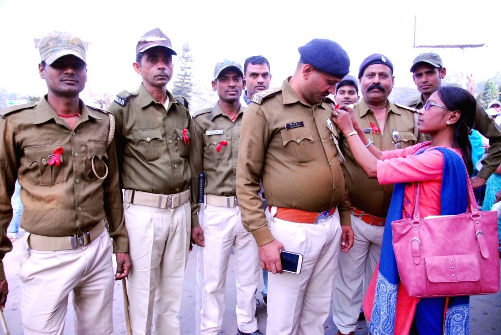 A woman pins a a red ribbon on a police personnel during an awareness rally organised on the occasion of World AIDS Day in Patna, on Dec 1, 2018.