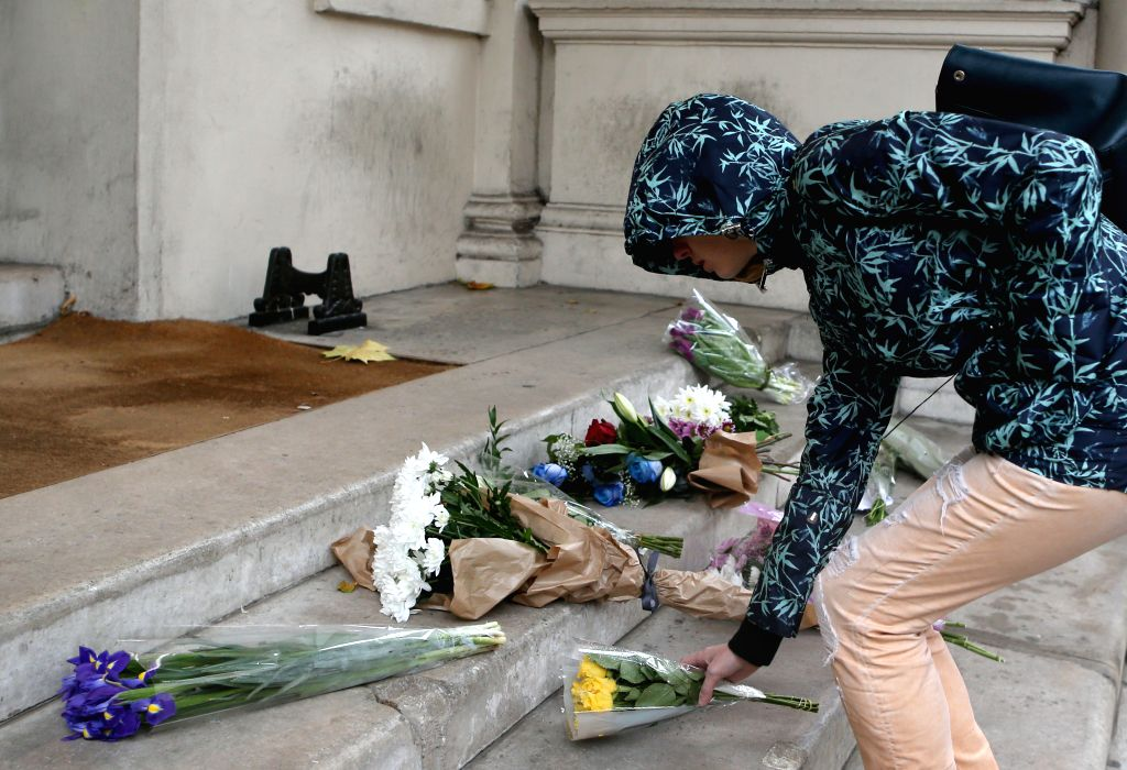A woman places flowers in front of the French Embassy in London, Great Britain, to mourn the victims of a series of attacks in Paris, on Nov. 14, 2015. (Xinhua/Han ...