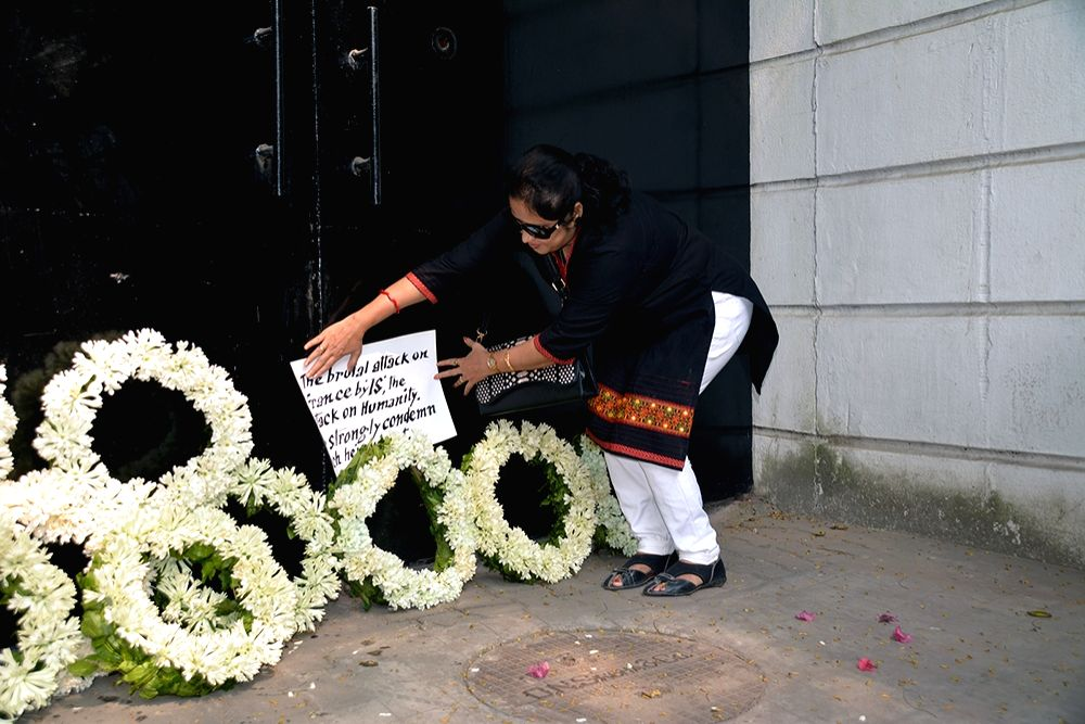 A woman places flowers in front of the French Embassy consulate to mourn the victims of a series of attacks in Paris; in Kolkata on Nov 15, 2015.