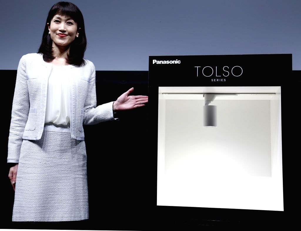 """A woman poses for photos with Japanese electronics giant Panasonic's new LED lighting product """"TOLSO"""" in Tokyo, Japan, June 26, 2015. Panasonic has put the ..."""