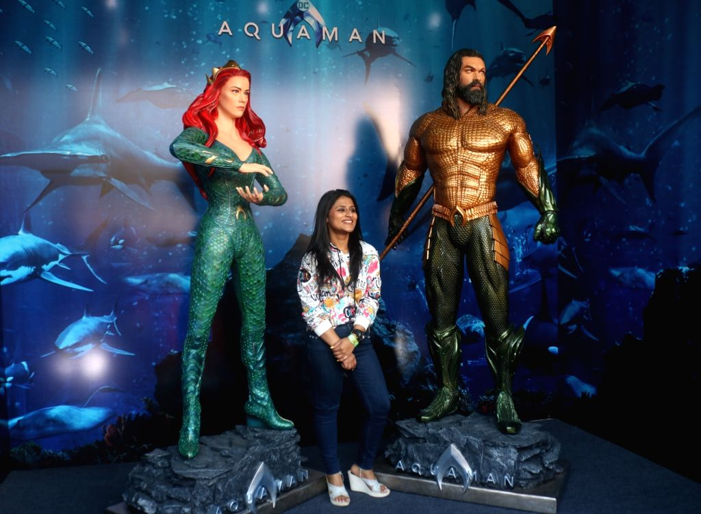 "A woman poses with the model of comic book character ""Aquaman"" at the three-day fest - ""Comic Con"" in New Delhi on Dec 8, 2018."
