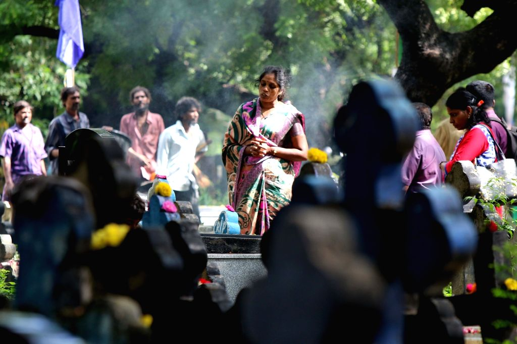 A woman prays besides the grave of her relative at a cemetery during the observance of All Souls' Day in Chennai, on Nov 2, 2018.