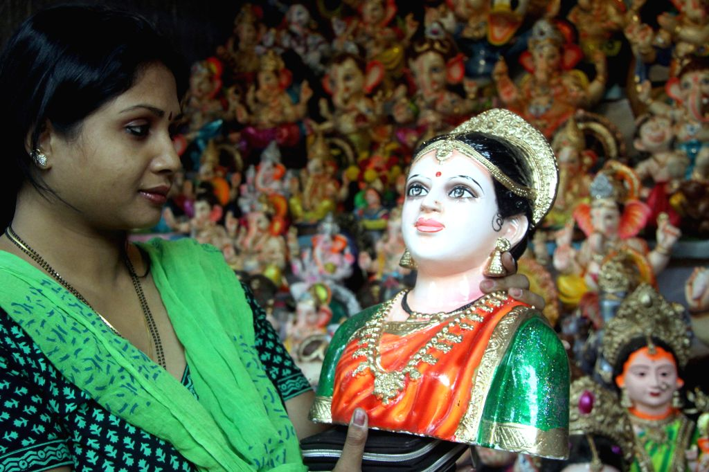A woman purchases a Gouri idol on the eve of Gauri Ganesha Festival at Malleshwaram in Bangalore on Aug 27, 2014.