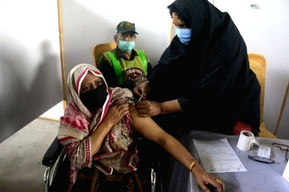 A woman receives a dose of COVID-19 vaccine at a vaccination center in Lahore, Punjab province, Pakistan, April 7, 2021.