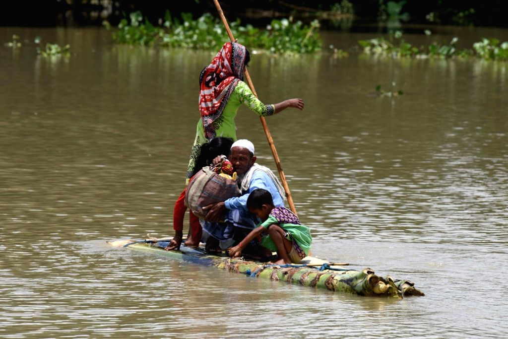 A woman rows a raft made up of banana trunk on flood waters in flood hit Morigaon district on July 5, 2017.