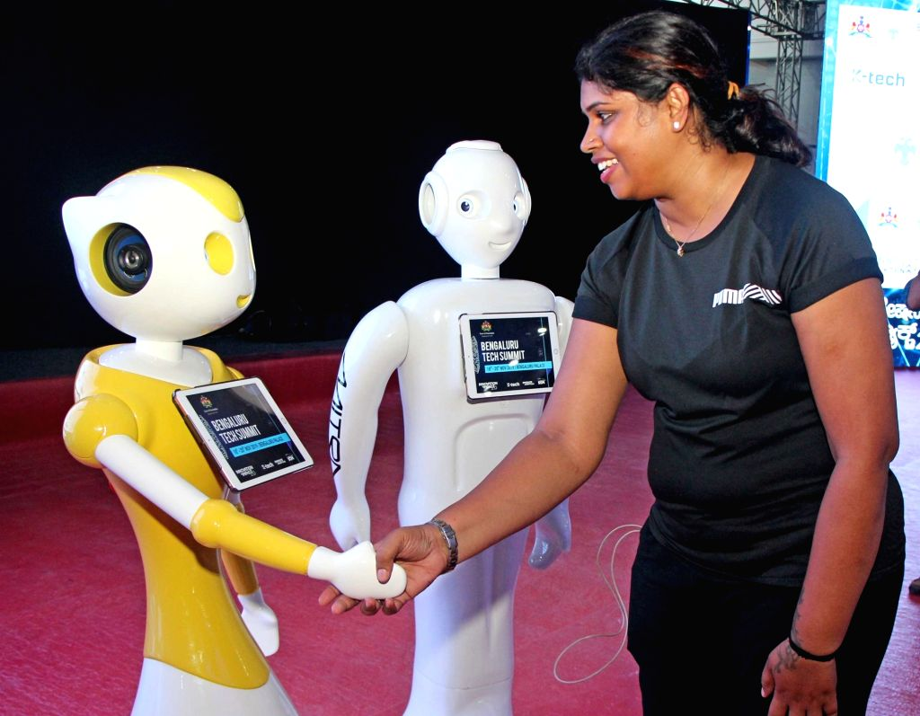 "A woman shaking hands with a robot during ""Bengaluru Tech Summit"" in Bengaluru on Nov. 17, 2019."