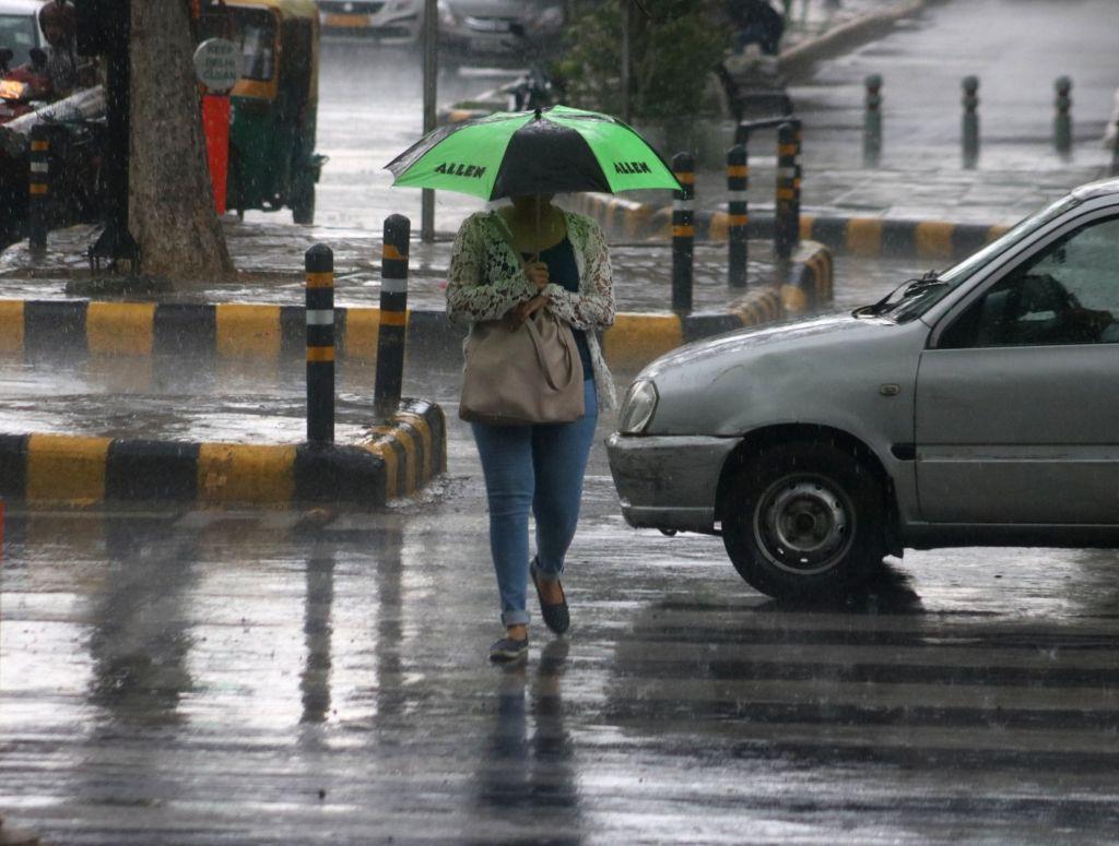 A woman shields herself with an umbrella as rains lash Delhi on July 16, 2018.