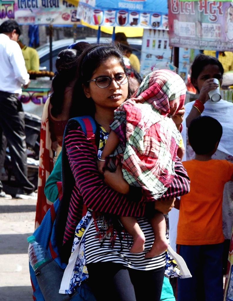 A woman shields the child in her arms from the scorching sun on a hot day in Patna, on April 15, 2019.