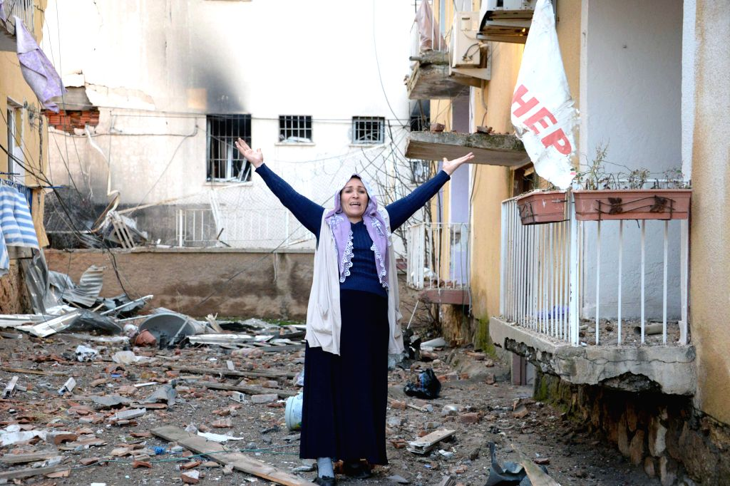 A woman shouts beside a damaged house in Turkey's southeastern Diyarbakir Province, on Jan. 14, 2016. Five people were killed and 39 others wounded in a car bomb ...