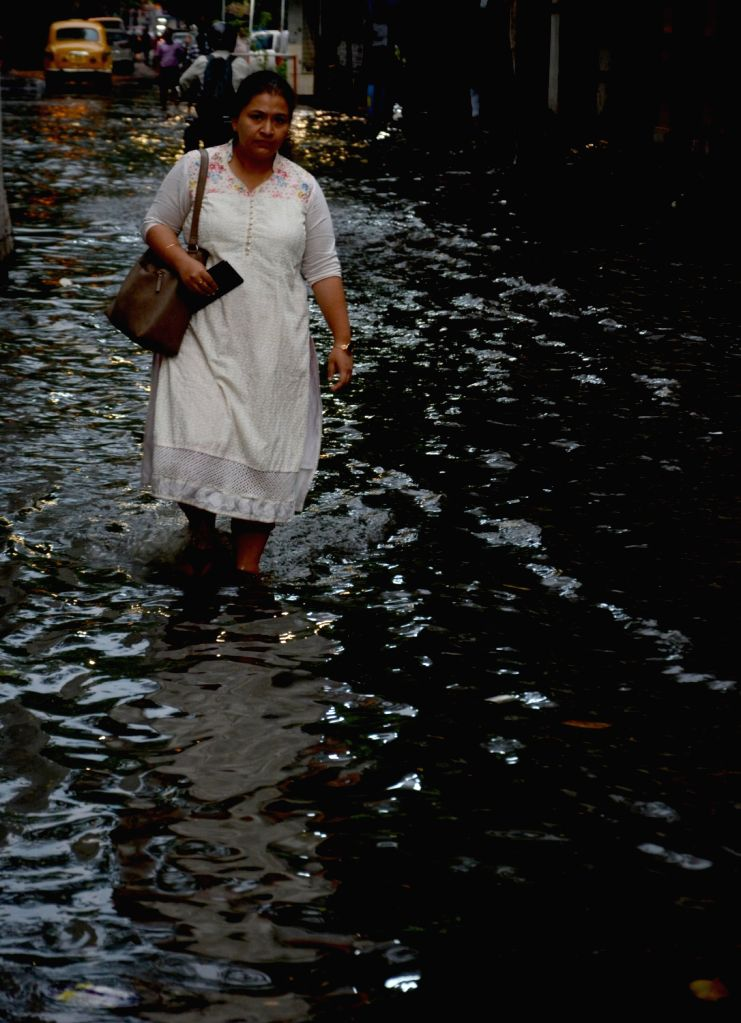 A woman struggles through a water-logged street after heavy rains in Kolkata, on Oct 9, 2019.