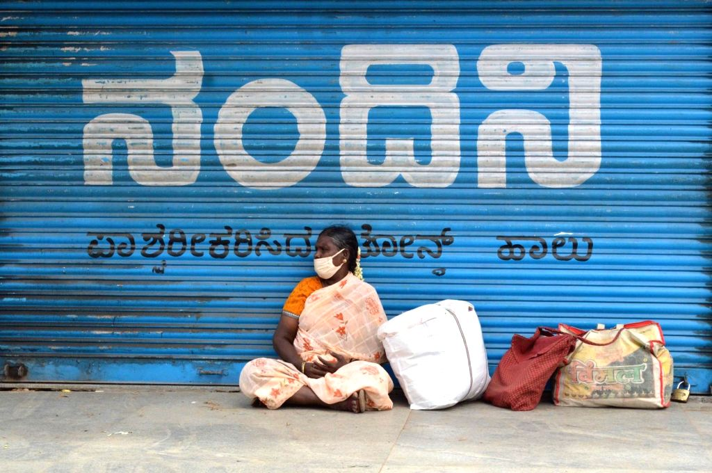 A woman sts in front of a closed store at KR Market during a strict lockdown that has been re-imposed for 15 days in five wards across Bengaluru to contain the spread of COVID-19 and ...