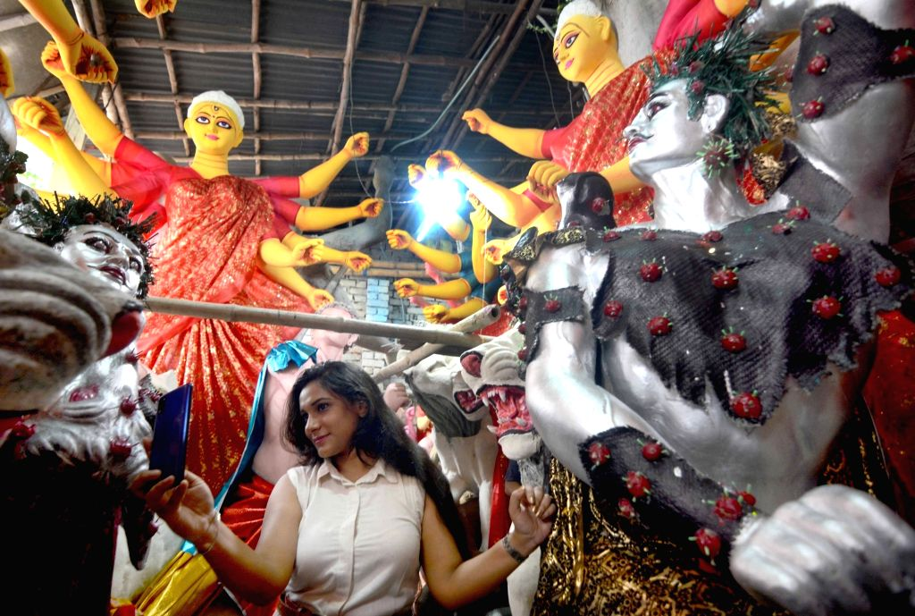 A woman take selfie in front of the Idol of Goddess Durga and Asur which the demon is creating what looks like a Delta variant virus at Kumortuli workshop in Kolkata on October 01, 2021.
