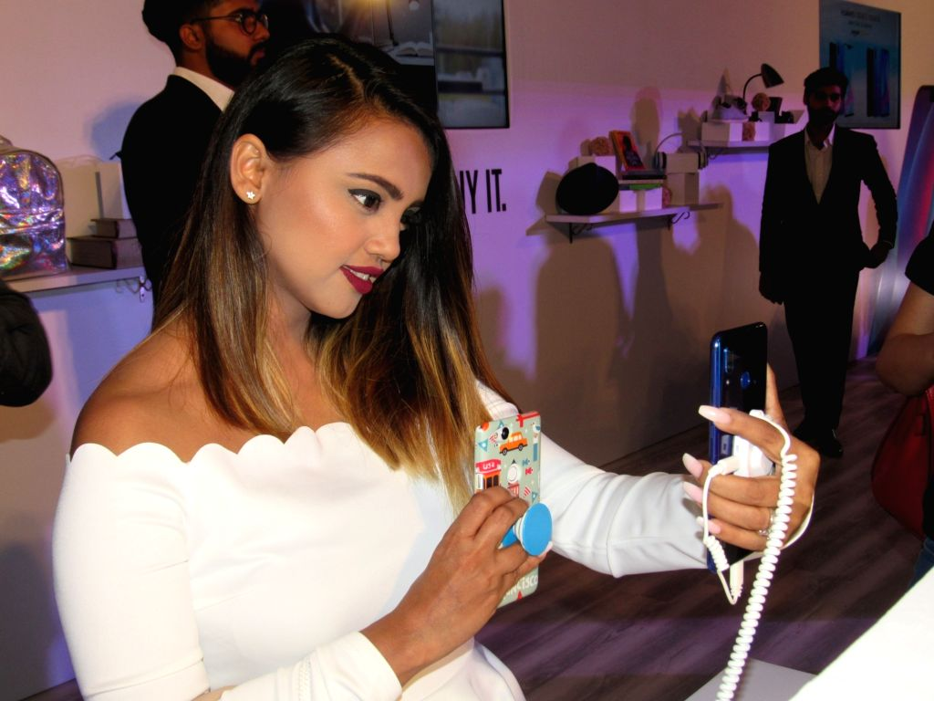 A woman takes a selfie with a newly launched Nova smatphone at the launch of  in New Delhi on July 26, 2018. Huawei Consumer Business Group (CBG) on Thursday brought to India two ...
