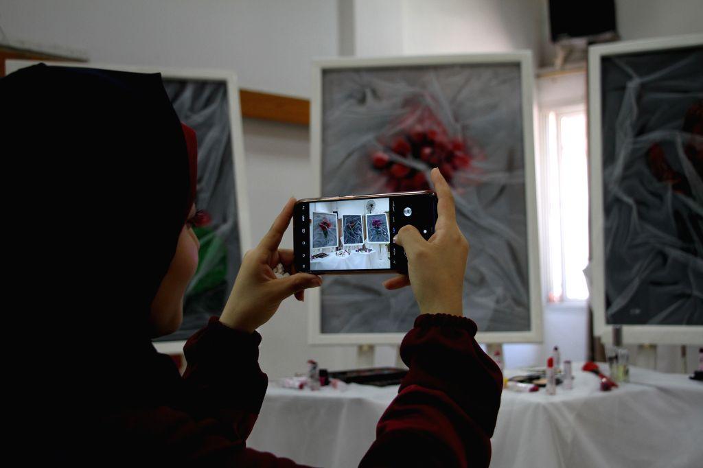 A woman takes photos of artworks at an exhibition of Palestinian artist Kholoud al-Dasooqi in Gaza City, on Aug. 11, 2020. Kholoud al-Dasooqi, a Palestinian artist ... - Kholoud