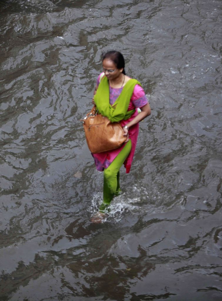 A woman wades through flooded streets of  Mumbai after heavy rains in Mumbai on July 16, 2014.