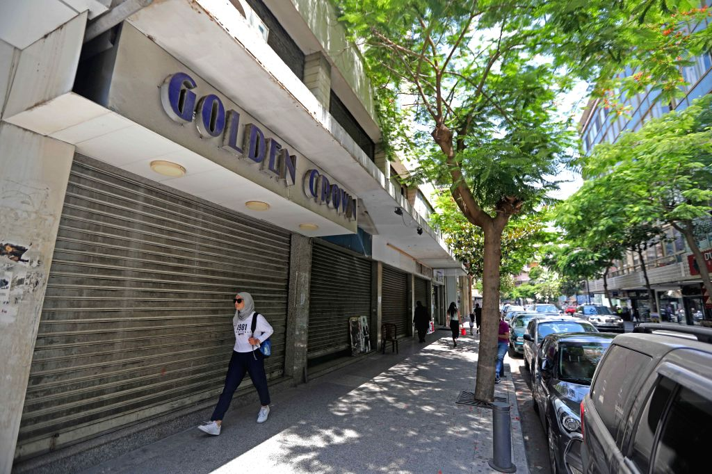 A woman walks by closed shops in Beirut, Lebanon, July 2, 2020. Lebanon's number of COVID-19 infections increased on Thursday by eight to 1,796 while the death toll ...