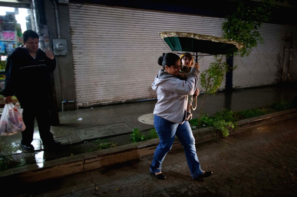 """A woman walks in the rain caused by the huricane """"Patricia"""" in Ameca, Jalisco state, Mexico, on Oct. 23, 2015. An hour after Hurricane Patricia made ..."""