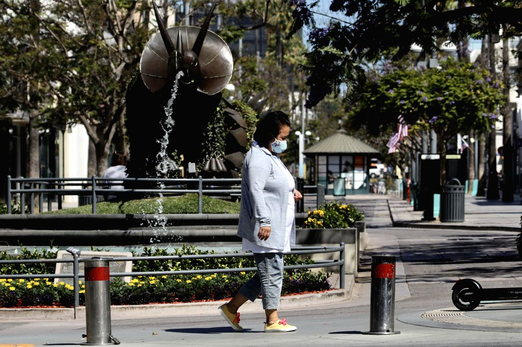 A woman walks on a street in Los Angeles County, the United States, on July 4, 2020. Nearly all Los Angeles County beaches have been closed for the Fourth of ...