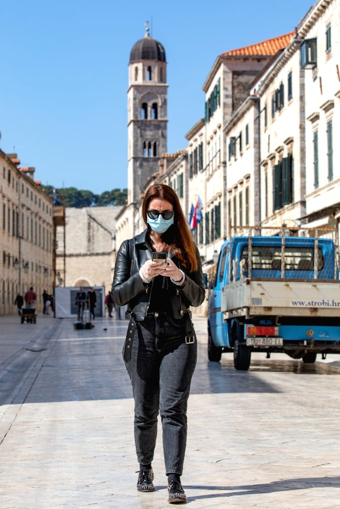A woman walks on the main street of the Old Town of Dubrovnik in Croatia on March 19, 2020. Croatia has so far confirmed 105 cases of COVID-19 infection since ...