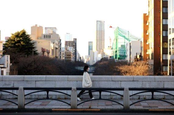 A woman wearing a face mask walks across a bridge in Tokyo, Japan, Dec. 31, 2020.